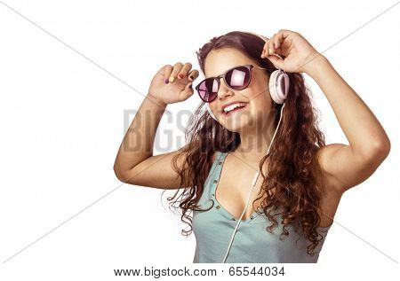 Pretty young girl with headphones and sunglasses dancing and smiling over white background