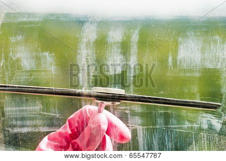 Hand In Pink Glove Cleans Window Glass By Squeegee