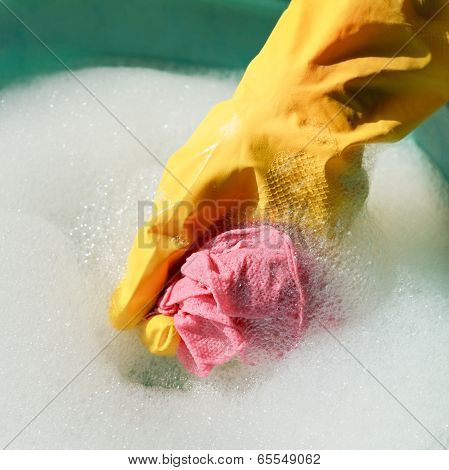 Hand In Yellow Rubber Glove Rinsing Wet Duster