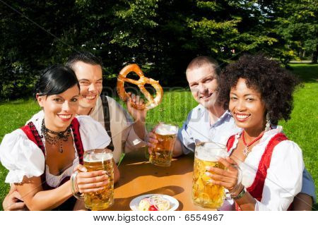 Group of four friends in beer garden eating and drinking