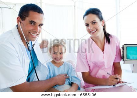 A Doctor Checking The Pulse On A Smiling Little Girl