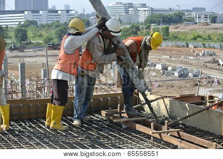 Three Construction Workers Using Hose from Elephant Pump