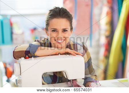 Portrait Of Smiling Seamstress With Sewing Machine