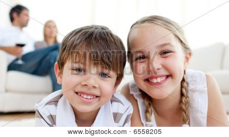 Smiling Siblings Lying On The Floor