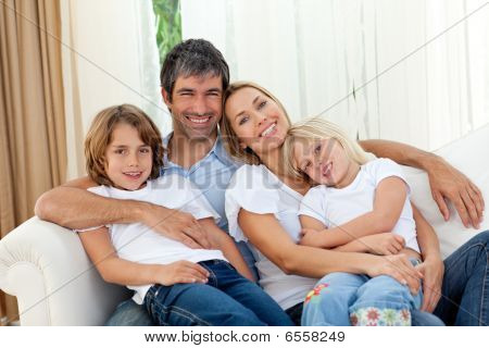 Smiling Family Relaxing On The Sofa