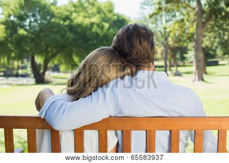Affectionate couple relaxing on park bench together on a sunny day