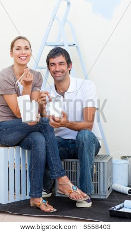Smiling Couple Eating While Decorating A Room