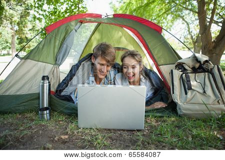 Cute couple lying in their tent using laptop on a sunny day