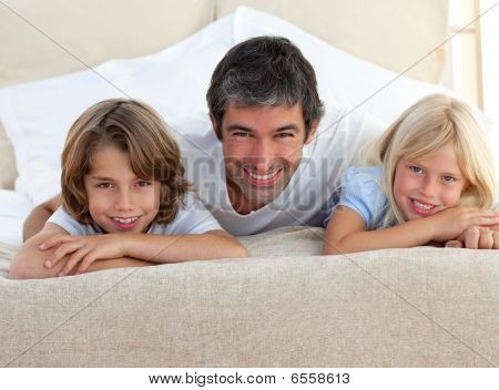 Caring Father And His Children Lying On A Bed