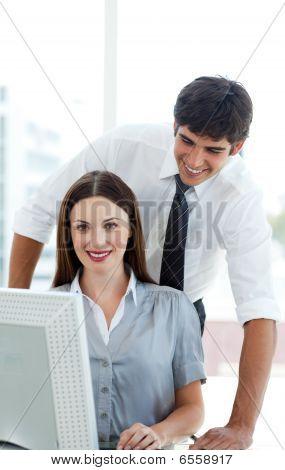 Compañeros de trabajo atractivos en una computadora