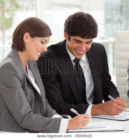 Two Smiling Colleagues Studying Sales Report With Their Team