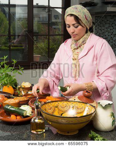 Moroccan immigrant woman in modern European kitchen preparing traditional tajine dish for Ramadan nights