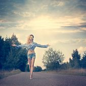 foto of independent woman  - Beautiful Woman with Open Arms under the Sunrise Walking on the Country Road - JPG