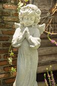 picture of garden sculpture  - praying and smiling little angel sculpture in the garden - JPG