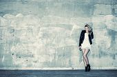 stock photo of crossed legs  - Beautiful urban girl leans against a concrete wall cross processed image