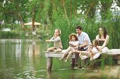 stock photo of ponds  - Young happy family with kids fishing in pond in summer - JPG