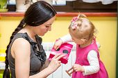 foto of montessori school  - Mother and child girl playing in kindergarten in Montessori preschool Class - JPG