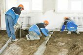 foto of floor covering  - Plasterer workers at indoor concrete cement floor topping with float - JPG