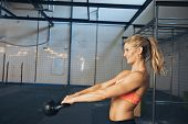 stock photo of kettling  - Side view of happy young woman exercising with kettle bell at gym. Caucasian female athlete doing crossfit workout at gym.