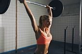 stock photo of dumbbells  - Strong woman lifting barbell as a part of crossfit exercise routine. Fit young woman lifting heavy weights at gym.