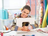 stock photo of sewing  - Happy seamstress embracing sewing machine in studio