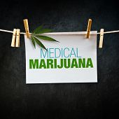 stock photo of ganja  - Medical marijuana title printed on paper hanging on clothesline - JPG