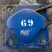 picture of bollard  - number sixty nine on a blue painted metal bollard - JPG