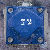 stock photo of bollard  - number seventy two on a blue painted metal bollard - JPG
