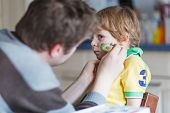 stock photo of brazilian carnival  - Father painting brazilian flag on face of little son for football or soccer game - JPG