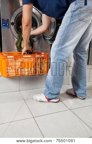 Low section of young man with basket putting clothes in washing machine at laundry
