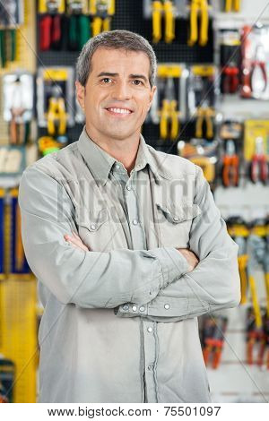 Portrait of happy mature man standing arms crossed in hardware store