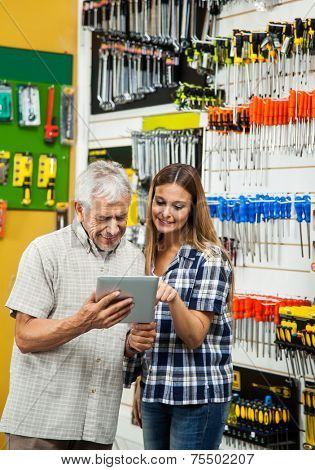 Smiling father and daughter using tablet computer in hardware store