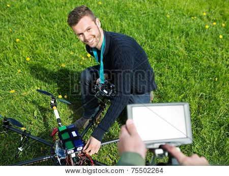 High angle view of happy young engineer fixing UAV helicopter in park