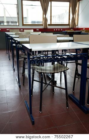 Interior of desks and chairs arranged in a row at classroom