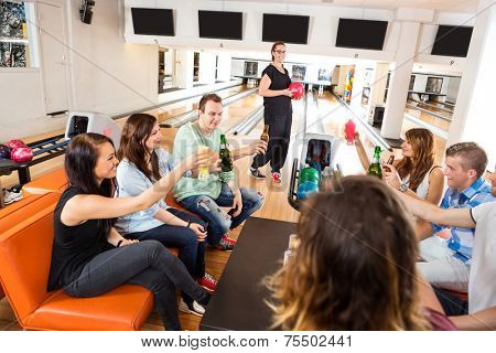 Group of young friends toasting drinks in bowling club