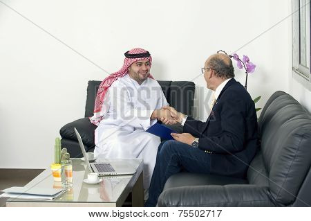 Senior Businessman Shaking hands with a muslim man, Multiracial Businesspeople shaking hands in offi