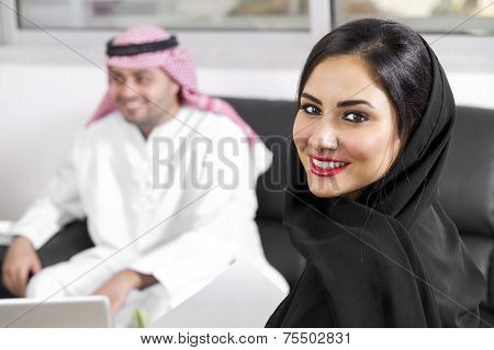 Arabian Businesswoman wearing hijab with her boss in background, Arabian businesspeople in office