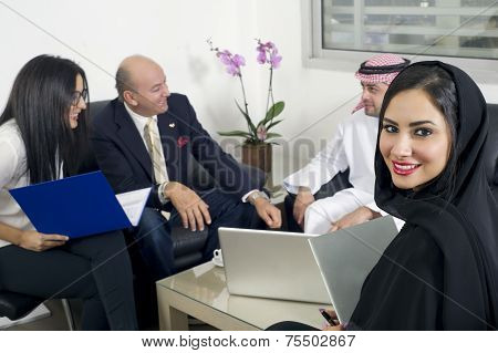 Arabian Businesswoman in office with Businesspeople meeting in the background, Arabian woman wearing