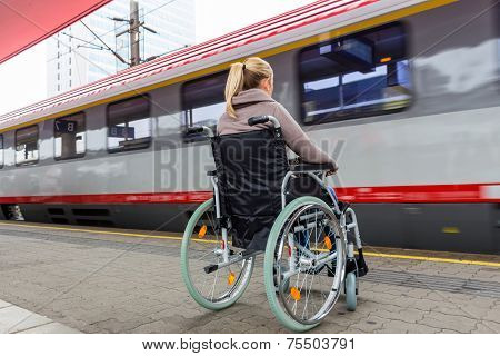 a young woman sitting in a wheelchair at a train station
