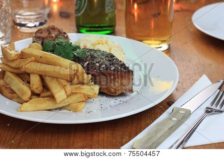 Piece of steak with french fries, cole slaw and fried garlic.