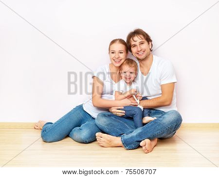 Happy Family On  Floor Near  Empty  Wall In The Apartment Bought On Mortgage