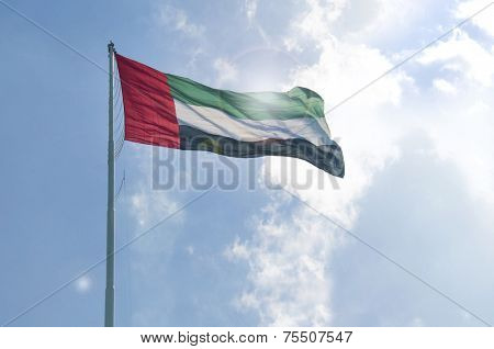 A big flag of UAE flying high in the sky. UAE celebrates National Day on 2nd December every year.