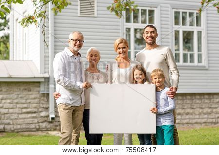 family, happiness, generation, home and people concept - happy family standing in front of house with white blank board outdoors