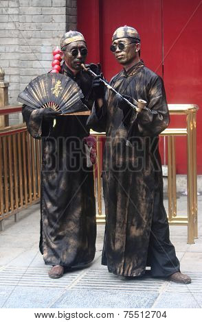 two street artists in specific costums and with painted faces make performance