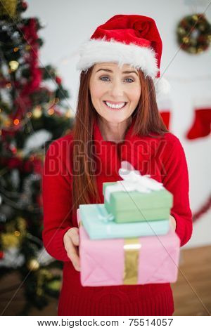 Festive redhead holding christmas gifts at home in the living room