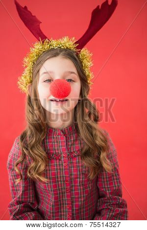Festive little girl wearing red nose on red background