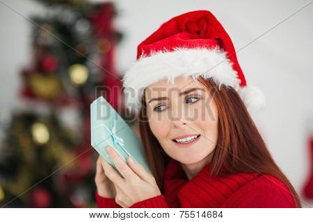 Festive redhead holding christmas gift at home in the living room