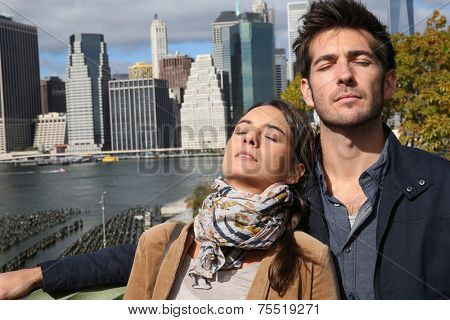 Couple relaxing by the Hudson River, South Manhattan in background