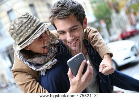 Cheerful couple having fun playing with smartphone