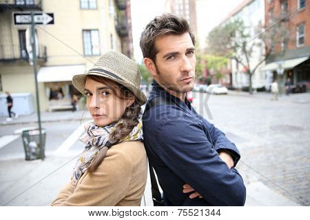 Couple in street leaning back to back